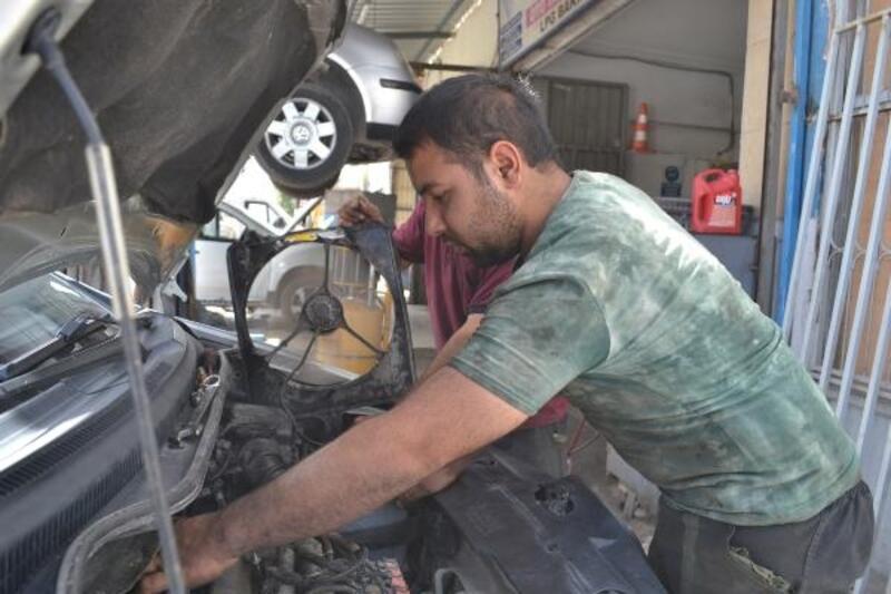 Sıcaktan bunalan tamirci, araç fanıyla serinledi