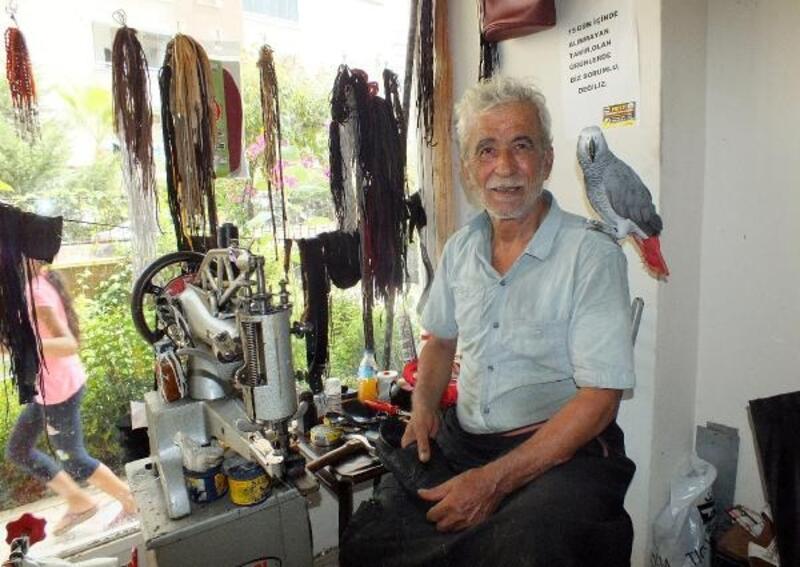 Omzunda papağanıyla ayakkabı tamir ediyor